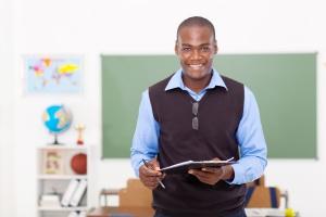 male African school teacher holding a clipboard